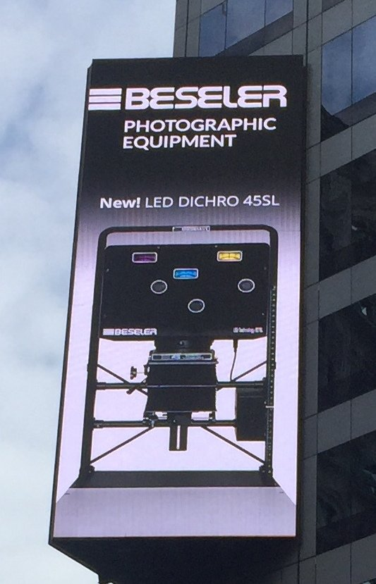 a photography advertisement attached to a building in times square